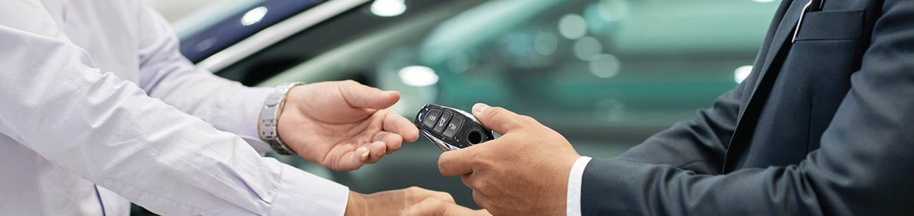two people in a handshake exchanging keys to a new car